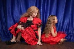 Mamman och dottern är kränkta och sitta på golvet mamman försöker att upprätta fred och kamratskap med barnet royaltyfri foto