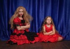 Mamman och dottern är kränkta och sitta på golvet mamman försöker att upprätta fred och kamratskap med barnet arkivbilder