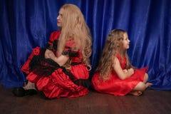 Mamman och dottern är kränkta och sitta på golvet mamman försöker att upprätta fred och kamratskap med barnet arkivbild