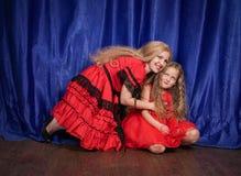 Mamman och dottern är kränkta och sitta på golvet mamman försöker att upprätta fred och kamratskap med barnet royaltyfri fotografi