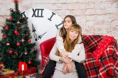 Mamman och dottern är lyckliga tillsammans på jul Arkivbild