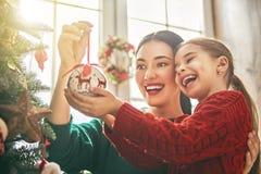 Mamman och dottern dekorerar julgranen royaltyfri foto
