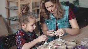 Mamman och dottern gör hantverk från lera Kurs i krukmakeri barnet är intensivt på idérikt arbete lager videofilmer