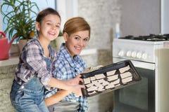Mamman och dottern gör kakor i köket arkivbilder