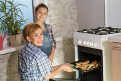 Mamman och dottern gör kakor i köket royaltyfri fotografi