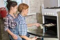 Mamman och dottern gör kakor i köket royaltyfria foton