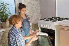 Mamman och dottern gör kakor i köket fotografering för bildbyråer