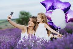 Mamman och dottern gör selfie på smartphonen i lavendelfältet härdar för fågelbegreppsfamilj älskvärda många för hustangentföräls Royaltyfri Bild