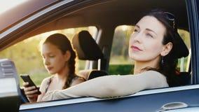 Mamman och dottern 11 gamla år vilar i bilen i ett pittoreskt ställe på solnedgången En kvinna ser bilfönstret