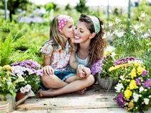 Mamman och dottern har gyckel i arbetet av att arbeta i trädgården Royaltyfri Bild