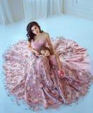 Mamman och dottern i lyxigt, rosa färgklänningar med sakura blommar på en kjol Familjkläder, identiska klänningar _ royaltyfri foto