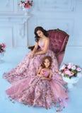 Mamman och dottern i lyxigt, rosa färgklänningar med sakura blommar på en kjol Familjkläder, identiska klänningar _ Royaltyfri Bild