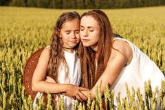 Mamman och dottern kramar i sommaren på ett vetefält royaltyfria bilder