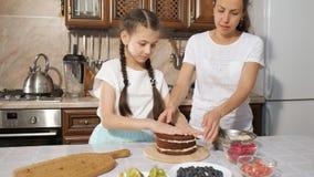 Mamman och dottern lagar mat den handgjorda kakan med kräm tillsammans arkivfilmer