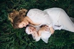 Mamman och dottern ligger på julgranar Royaltyfria Bilder