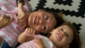 Mamman och dottern ligger på mattan, ler och bedrar omkring lager videofilmer