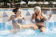 Mamman och dottern, medan bespruta vatten i en bubbelpool, badar Royaltyfria Bilder