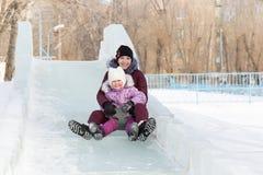 Mamman och dottern rider från ett snöig berg royaltyfri bild
