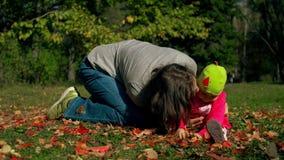 Mamman och dottern sitter i hösten på gräset och lek med stupade röda och gula sidor lager videofilmer