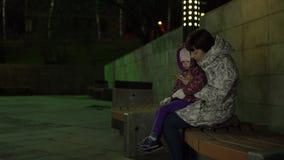 Mamman och dottern sitter på en bänk och använder telefonen på natten i parkera stock video