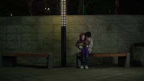 Mamman och dottern sitter på en bänk och använder telefonen på natten i parkera arkivfilmer