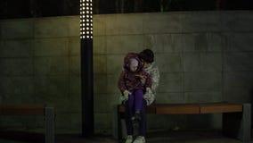 Mamman och dottern sitter på en bänk och använder telefonen på natten i parkera lager videofilmer