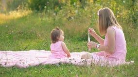 Mamman och dottern sitter på gräsmattan lager videofilmer