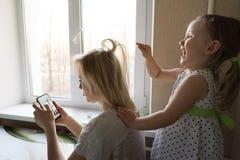 Mamman och dottern sitter vid f?nstret royaltyfri fotografi
