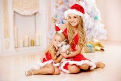 Mamman och dottern som kläs som jultomten, firar jul Familj på Arkivfoton