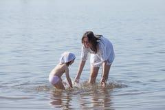 Mamman och dottern spelar i floden royaltyfri foto