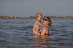 Mamman och dottern spelar lyckligt på havet Royaltyfria Foton