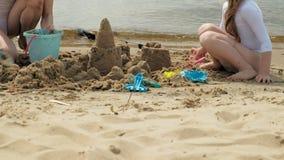 Mamman och dottern spelar på stranden som bygger en sandslott swallowtail f?r sommar f?r fj?rilsdaggr?s solig semester lager videofilmer