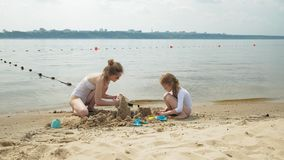 Mamman och dottern spelar på stranden som bygger en sandslott swallowtail f?r sommar f?r fj?rilsdaggr?s solig semester stock video