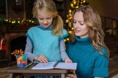 Mamman och dottern spenderar fritid tillsammans i vardagsrummet på julgranen draw royaltyfria foton