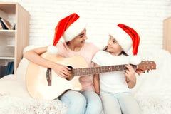 Mamman och dottern vilar hemma och spelar gitarren arkivbilder