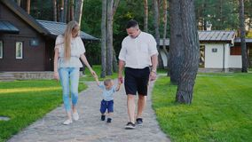 Mamman och farsan leder deras 1 åriga son Gå tillsammans i trädgården av huset steadicamskott stock video