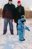 Mamman och farsan står se hans barn som nära strosar Arkivbilder