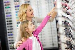 Mamman och flickan väljer den härliga ramen för glasögon arkivfoton