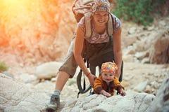 Mamman och hans lilla son klättrar i kanjonen Arkivfoto