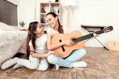 Mamman och hennes dotter sitter på det hemmastadda golvet och spelar gitarren De sjunger till gitarren royaltyfria foton