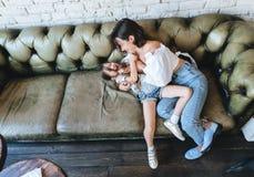 Mamman och hennes liten flicka har gyckel på soffan royaltyfri fotografi