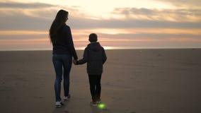 Mamman och hennes son promenerar kusten på solnedgången arkivfilmer
