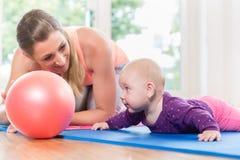 Mamman och hon behandla som ett barn övning som kryper i moder- och barnkurs Fotografering för Bildbyråer