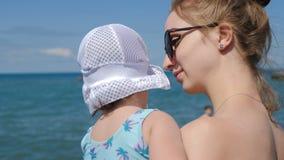 Mamman och litet charma behandla som ett barn flickan på stranden i sommar arkivfilmer