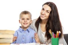 Mamman och sonen är le och krama, medan göra deras läxa F?r?lskelse och mjukhet Vit bakgrund arkivbild