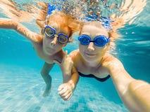 Mamman och sonen, i att dyka exponeringsglas, simmar i pölen under vattnet arkivfoton