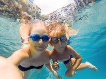 Mamman och sonen, i att dyka exponeringsglas, simmar i pölen under vattnet arkivbild