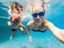 Mamman och sonen, i att dyka exponeringsglas, simmar i pölen under vattnet royaltyfria bilder