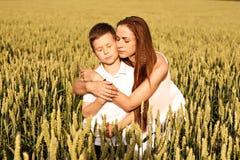 Mamman och sonen kramar i sommaren på ett vetefält royaltyfri foto