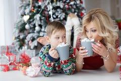Mamman och sonen ligger nära trädet för det nya året med stora koppar av cappuccino och marshmallower Arkivbilder